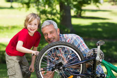 Happy father and his son fixing a bike Stock Image