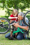 Happy father and his son fixing a bike Royalty Free Stock Photography