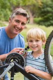 Happy father and his son fixing a bike Royalty Free Stock Image
