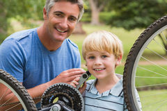 Happy father and his son fixing a bike Royalty Free Stock Images