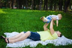 Happy father and his son on grass. Happy father and his son playing on grass, handsome men holding his child in his arms Stock Photo