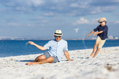 Happy father and his son having fun at the beach Stock Images