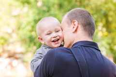 Happy father and his son outdoors. Child hugging daddy. Royalty Free Stock Image