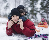 Happy father with his son outside with snowman Royalty Free Stock Photo