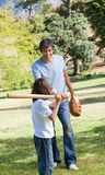 Happy father and his son playing baseball. In a park Royalty Free Stock Images