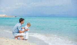Happy father and his son playing at beach Stock Photos