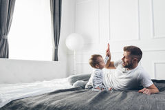 Happy father with his son playing at home on the bed. Happy father with his one year old son playing at home on the bed Stock Image
