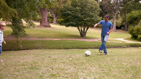 Happy father with his son playing soccer together