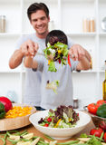 Happy father and his son preparing a salad Stock Photos