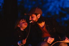 Happy father and his son sitting  on the logs in the forest in front of a fire and eating marshmallows from the sprigs stock photo