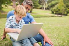 Happy father with his son using laptop in the park Royalty Free Stock Photography