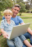 Happy father with his son using laptop in the park Royalty Free Stock Images