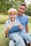 Happy father with his son using tablet in the park Stock Images