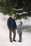 Happy father with his son walks through the park in the snowy winter weather.  Stock Photos