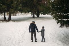 Happy father with his son walks through the park in the snowy winter weather.  Royalty Free Stock Photos