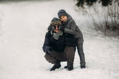 Happy father with his son walks through the park in the snowy winter weather.  Royalty Free Stock Photo