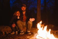 Happy father and his son warm themselves by the fire sitting in an embrace on logs in a hike in the forest at the night. stock image
