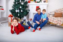 Happy father and his sons are sitting at home near the Christmas tree with gifts Stock Photo