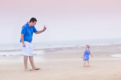 Happy father with his toddler daughter on beach Stock Photos