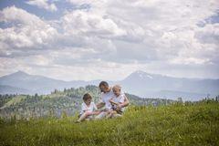 Happy father with his two young sons sitting on the grass on a background of green forest, mountains and sky with clouds. stock images