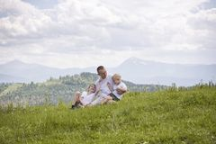 Happy father with his two young sons sitting on the grass on a background of green forest, mountains and sky with clouds. royalty free stock photography