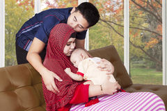 Happy father with his wife and cute baby. Young father kiss his wife at home with their baby sleeping on the mother's chest Royalty Free Stock Images