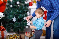 A happy father and his young son decorate the Christmas tree with white snowflakes. Stock Images