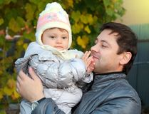 Happy father holding baby in hat stock images