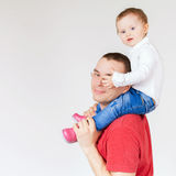 Happy father holding child at white background. Fashion baby. Looking at camera. Paternal care very important for baby. Custody. Rights Royalty Free Stock Photography