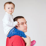 Happy father holding child at white background. Fashion baby. Looking at camera. Paternal care very important for baby. Custody. Rights Royalty Free Stock Image