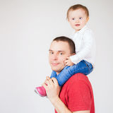 Happy father holding child at white background. Funny father holding child at white background. Fashion baby. Looking at camera. Paternal care very important for Royalty Free Stock Photo