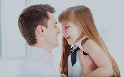Happy father holding daughter on hands laughing turned to his face. stock image