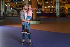 happy father holding daughter in roller skates stock photo