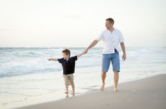 Happy father holding hand of little son walking together on the beach with barefoot Stock Photo