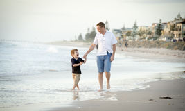 happy father holding hand of little son walking together on the beach with barefoot Royalty Free Stock Images