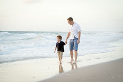 Happy father holding hand of little son walking together on the beach with barefoot Royalty Free Stock Photos