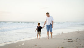 happy father holding hand of little son walking together on the beach with barefoot Royalty Free Stock Photography