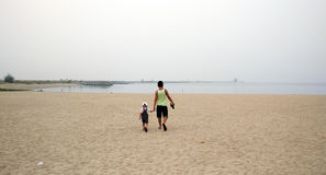 Happy father holding hand of little son walking together on the beach with shoes Stock Photo