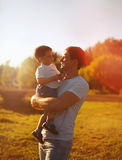Happy father holding on hands child son warm autumn evening, sunny family photo Stock Photos