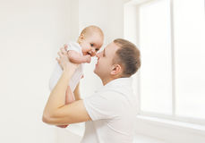 Happy father holding on hands his baby at home Stock Photos