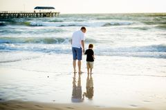 Happy father holding holding hand of little son walking together on the beach with barefoot Stock Photos