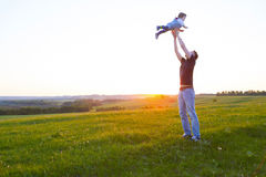 Happy father holding kid in arms, throwing baby in air. Royalty Free Stock Photo