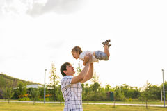 Happy father holding little kid in arms, throwing baby in air. concept of happy family, fatherhood Stock Photography