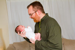 Happy Father Holding Newborn. A newborn baby boy is being held in the arms of his happy dad who is smiling Royalty Free Stock Photo