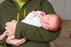 Happy Father Holding Newborn. A newborn baby boy is being held in the arms of his happy dad who is smiling Stock Images