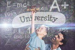 Composite image of happy father holding son. Happy father holding son against university against black background Stock Images