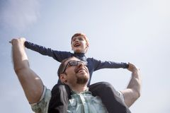 Happy father holds his son on his shoulders. The concept of fatherhood royalty free stock photos