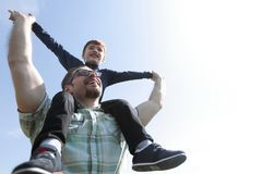 Happy father holds his son on his shoulders. The concept of fatherhood royalty free stock photography