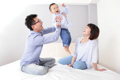 Happy father hug his son at home. Happy father hug his son with smile mother sitting on bed at home, asian family Stock Photography