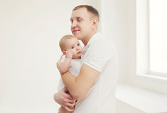 Happy father hugging his baby at home Stock Images